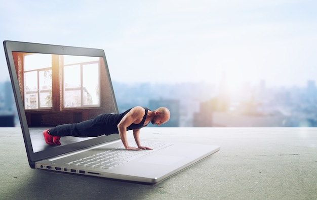 Personal trainer doet gymles via internet en laptop