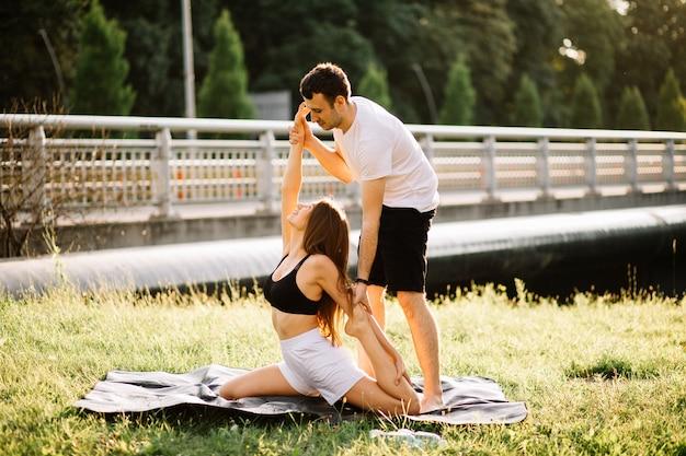 Personal trainer man coaching jonge vrouw, yoga op stadsgazon, zomeravond, fit