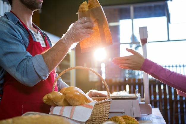 Personeel dat pakketbrood aan klant geeft