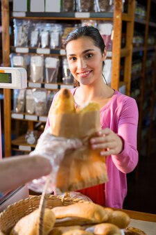 Personeel dat pakketbrood geeft aan vrouw