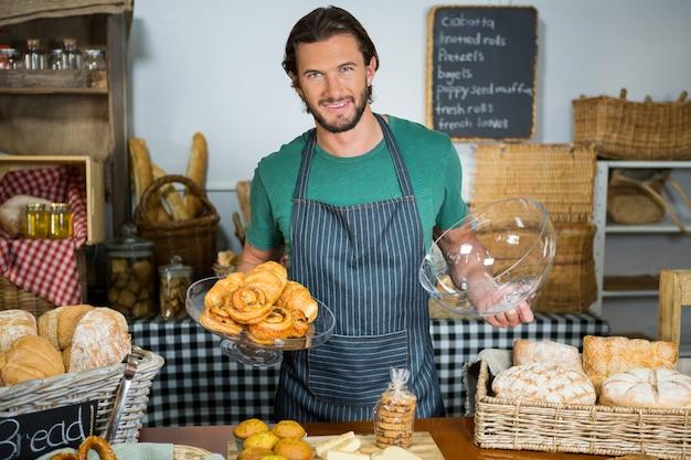Personeel met dienblad met croissant aan balie