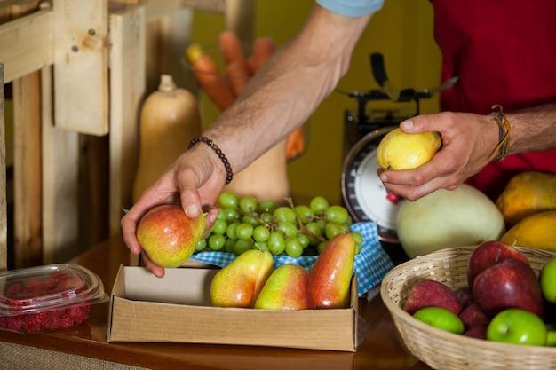 Personeel schikken groenten aan balie in markt