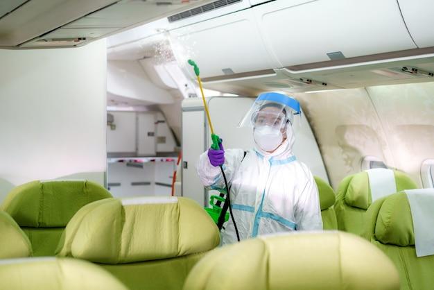 Personeel van de vrouwelijke luchtvaartmaatschappij in beschermend pak (pbm) draagt een medisch gezichtsmasker desinfecterende spray voor covid-19 of coronavirus in de vliegtuigcabine na of voor de landing of opstijgen om ziektepreventie te voorkomen