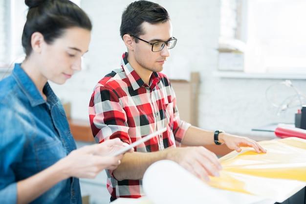 Personeel van drukkerij werken met kleurrijke papier