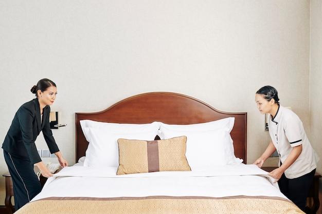 Personeel van het hotel dat het bed opmaakt