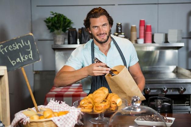 Personeel verpakt een croissant in een papieren zak aan de balie
