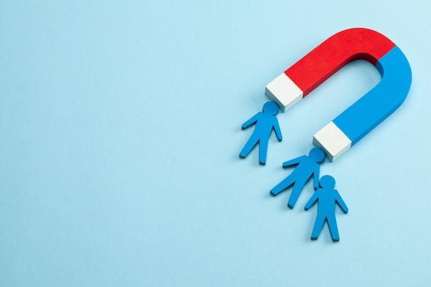 Personeelswerving en een magneet trekken goede werknemersleiders aan. blauwe achtergrond.