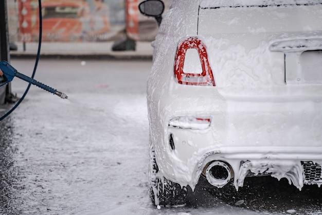 Persoon achter de schermen wast persoonlijke auto op zelfbedieningscarwash van slang. auto bedekt met water en zeep
