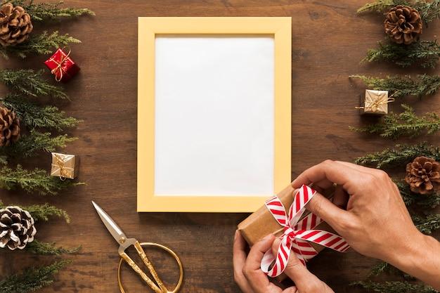 Persoon bindende strik op de doos van de gift van kerstmis