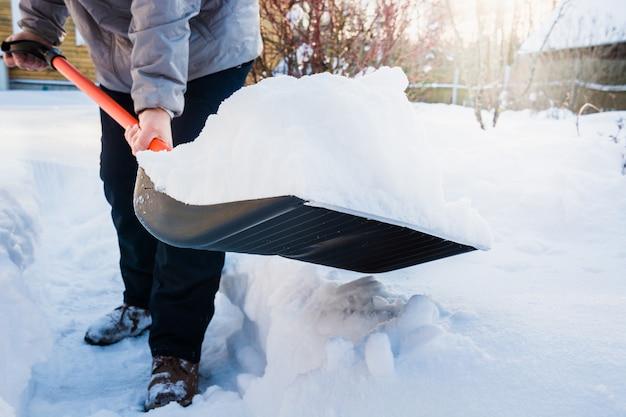 Persoon clearing sneeuw met schop