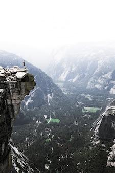 Persoon die aan de rand van een rotsachtige berg