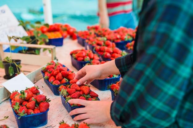 Persoon die aardbeien koopt bij de supermarkt