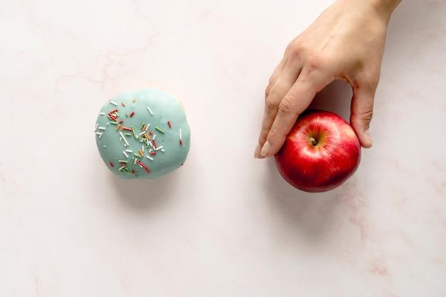 Persoon die appel over doughnut kiest tegen witte achtergrond