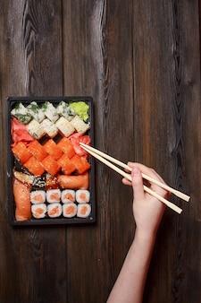 Persoon die aziatische voedselsushi met eetstokjes eet