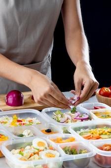 Persoon die batchcooking met gezond voedsel beoefent