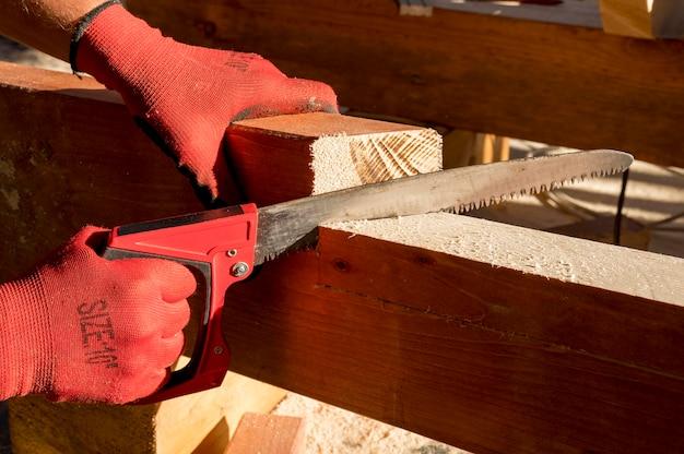 Persoon die beschermende handschoenen draagt en een boormachine gebruikt