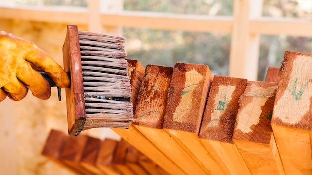 Persoon die beschermende handschoenen draagt en het hout lakt