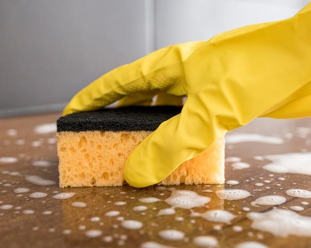 Persoon die beschermende handschoenen draagt met een spons