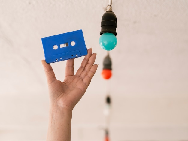 Persoon die blauwe cassetteband houdt dichtbij multicolored gloeilampen