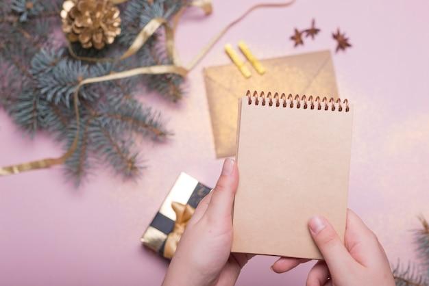Persoon die blocnote boven de kerst tafel