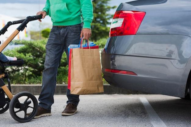 Persoon die boodschappentassen in de auto houdt