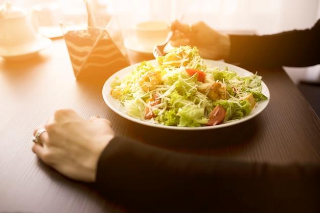 Persoon die caesar salade met garnalen in restaurant eet