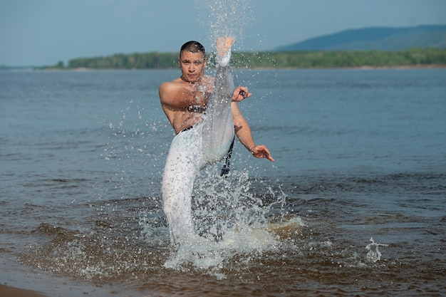 Persoon die capoeira op het strand uitoefent