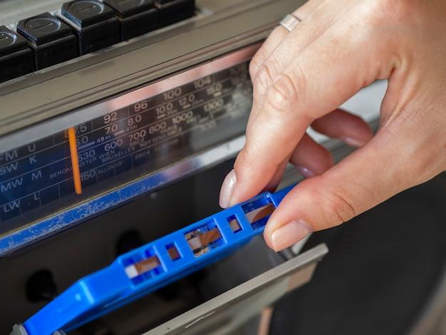 Persoon die cassetteband plaatst in uitstekende speler