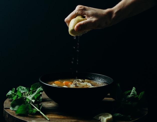 Persoon die citroen op soep in een zwarte kom met een donkere muur drukt