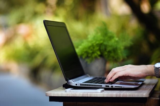 Persoon die computernotitieboekje gebruikt dat thuis werkt