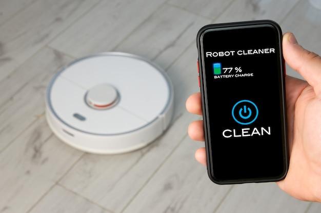 Persoon die de afstandsbediening van een robotstofzuiger op zijn smartphone gebruikt