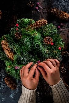 Persoon die de groene kroon van kerstmis met denneappels en rode de winterbessen verfraait