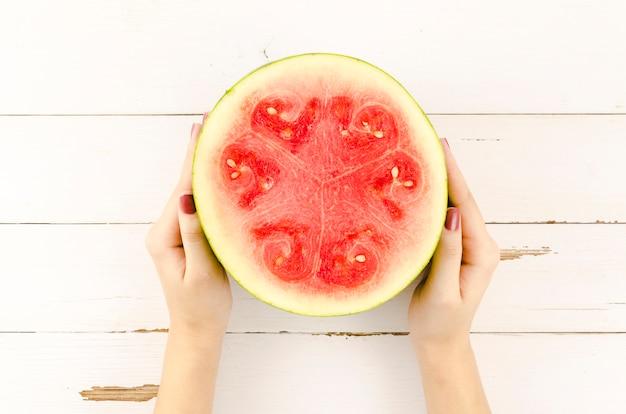 Persoon die de helft van verse watermeloen