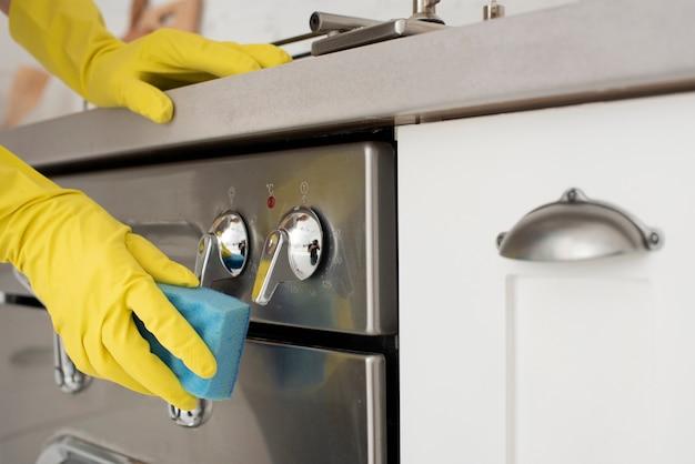 Persoon die de keuken met handschoenen schoonmaakt