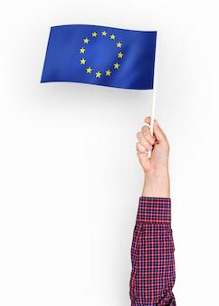 Persoon die de vlag van de europese unie zwaait