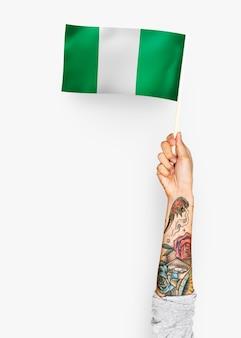 Persoon die de vlag van de federale republiek nigeria zwaaien