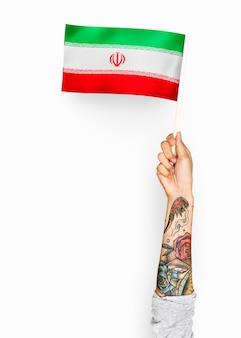 Persoon die de vlag van de islamitische republiek iran zwaaien