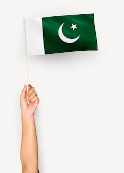 Persoon die de vlag van de islamitische republiek pakistan zwaaien