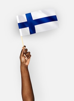 Persoon die de vlag van de republiek finland zwaaien