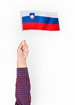 Persoon die de vlag van de republiek slovenië zwaaien Gratis Foto
