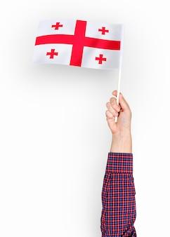 Persoon die de vlag van georgië zwaaien