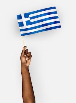 Persoon die de vlag van griekenland golft
