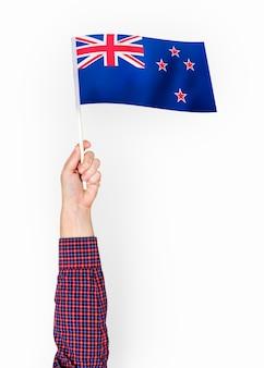 Persoon die de vlag van nieuw-zeeland zwaait