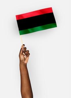 Persoon die de vlag van pan-african-vlag golft