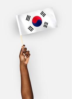 Persoon die de vlag van zuid-korea zwaaien