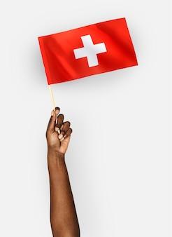 Persoon die de vlag van zwitserland zwaaien