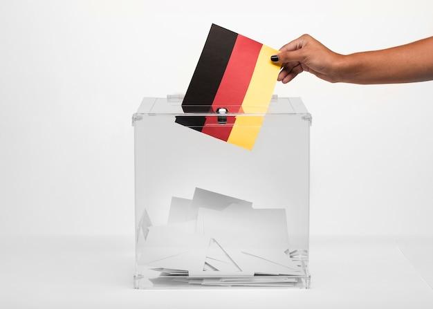Persoon die de vlagkaart van duitsland zet in stembus