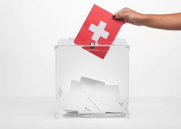 Persoon die de vlagkaart van zwitserland brengt in stembus