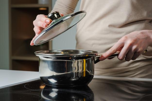 Persoon die deksel verwijdert uit kookpot