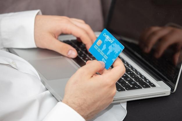 Persoon die details van zijn creditcard in laptop invoert